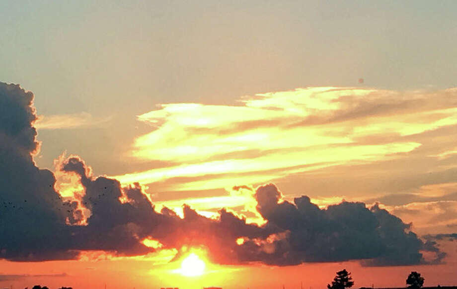Clouds try to block the sun as it sets in an orange sky. Photo: Joy Harris | Reader Photo