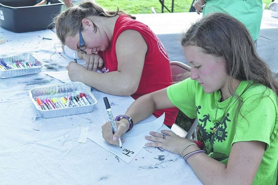Tylea McMillan (left), 16, and Lahia Critchelow, 16, both of Jacksonville, decorate penats Friday for the 2016 Community Project at the Jacksonville Main Street's Art Fair on the Square in Central Park.