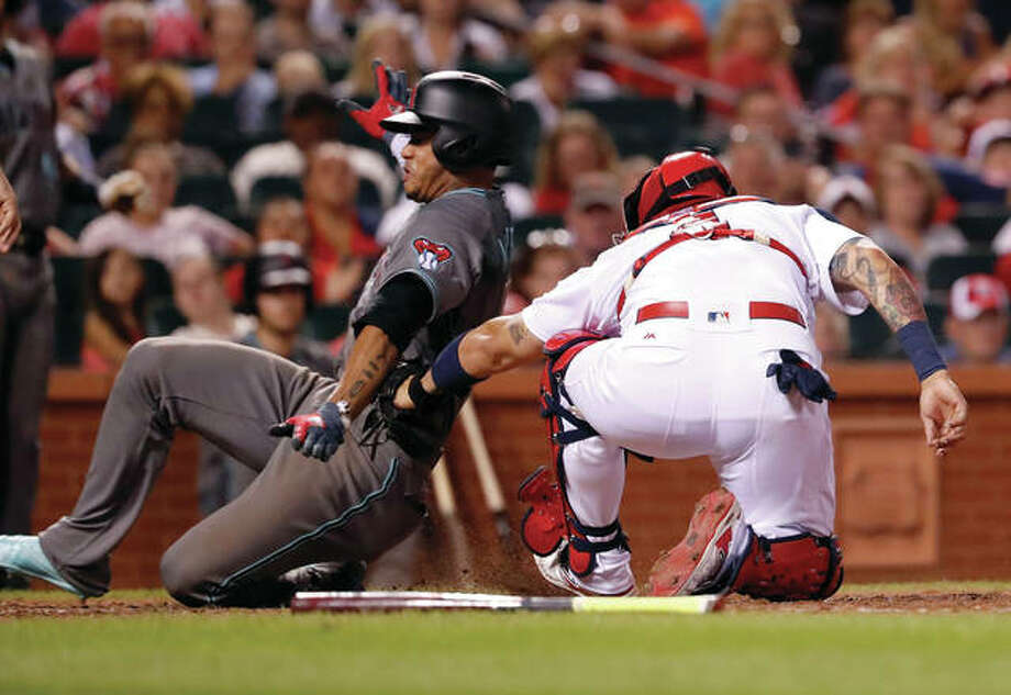 The Diamondbacks' Ketel Marte (left) is tagged out by Cardinals catcher Yadier Molina during the eighth inning to preserve the Cards' 1-0 lead that stood for the final Friday night at Busch Stadium.