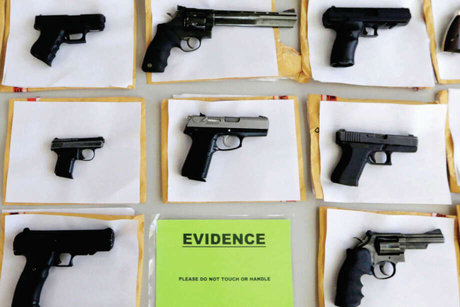 M. Spencer Green | AP A police display shows some of the thousands of illegal firearms confiscated during the year in the battle against gun violence. Hoping to stem the flow of illegal guns into Illinois, lawmakers have sent Gov. Bruce Rauner legislation that would punish firearm traffickers with prison sentences of up to 30 years.