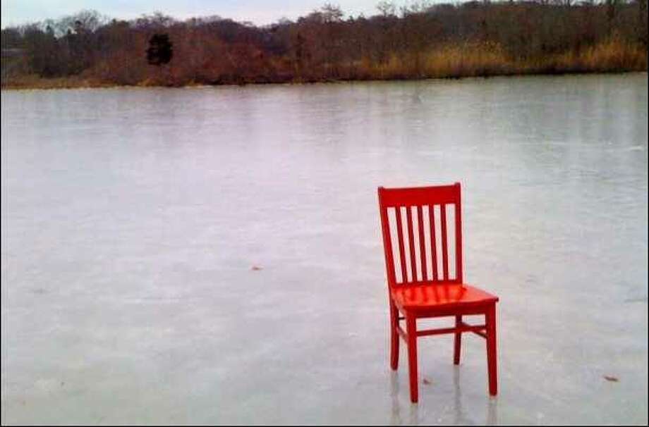 "Woods Hole Inn on Cape Cod innkeeper Beth Colt posted a picture on Facebook of her simple red chair perched on the ice behind her house and watched her page light up with ""likes."" This picture was shared on the Facebook page of a nature photographer from California, who was inspired by the image to visit the Woods Hole Inn and took an amazing second photo of the chair on a local beach. Photo: For The Telegraph"