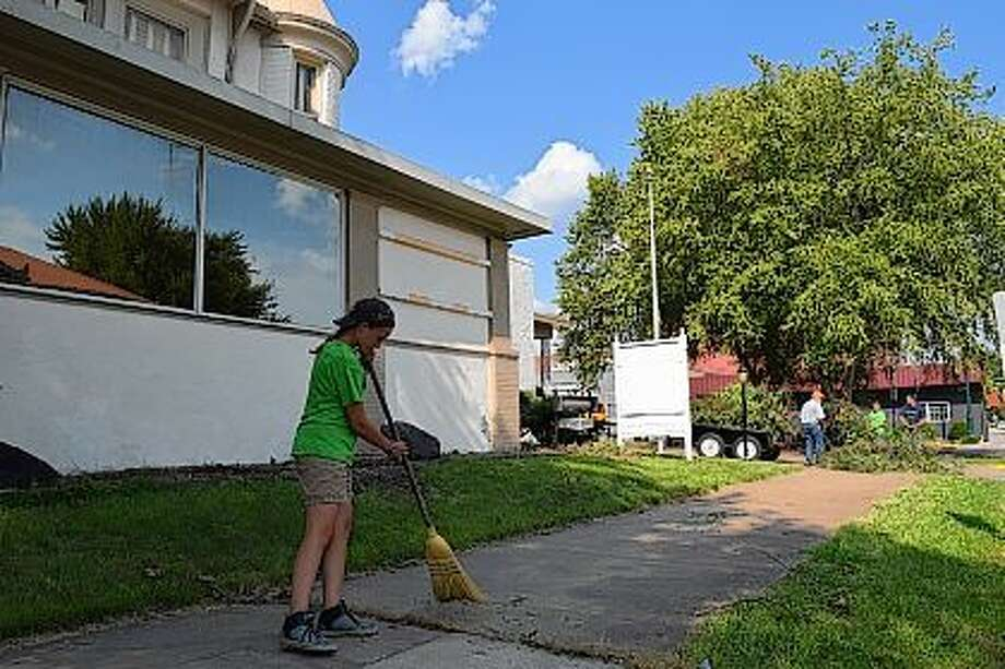 Jacksonville Dream Center Foundation member Lahia Critchelow of Jacksonville sweeps the sidewalk in front of the organization's new home on West College Avenue Wednesday as other members load brush onto a trailer. Photo: Greg Olson | Journal-Courier