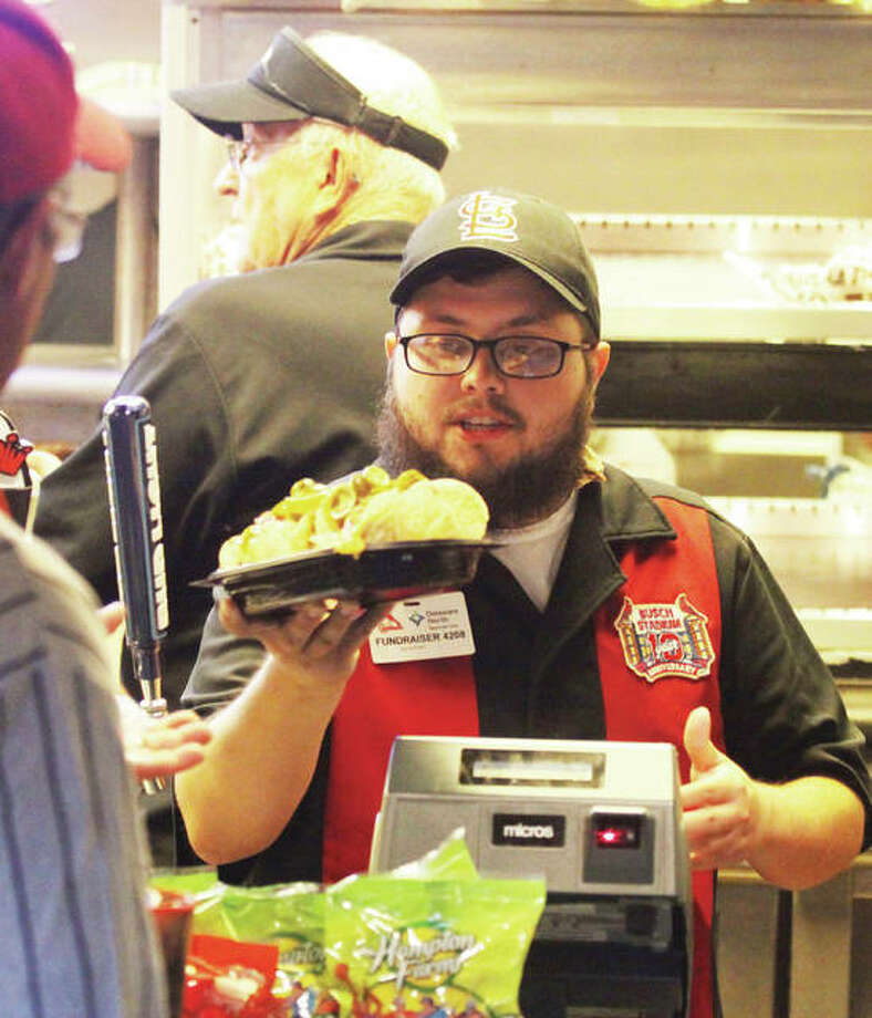 Jon Runyan hands an order of nachos to a customer at Busch Stadium while working as a volunteer fundraiser in a concession stand. Members of Wood River's Ivy Heights Church of God and Bethalto's Lifebrook Church of God have worked baseball games and concerts this summer to raise funds for their churches. Photo: Scott Cousins|The Telegraph