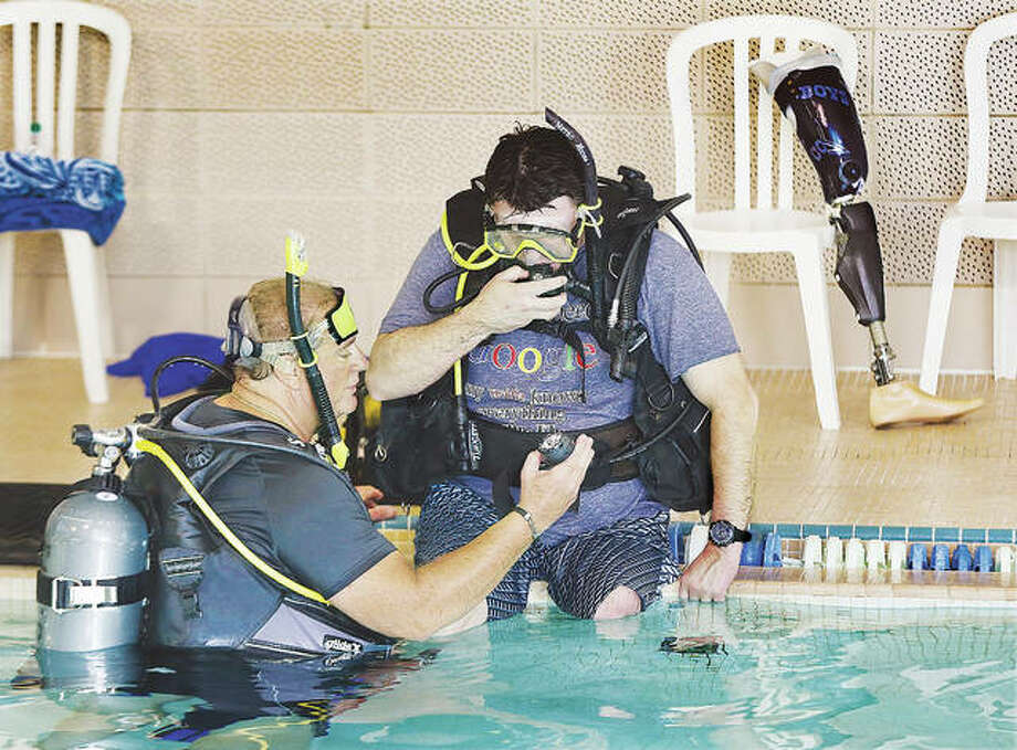 Instructor Dwight Tungett works with amputee Bobby Hutchinson, 45, of Glen Carbon, in the swimming pool at MaxSports in Alton. Hutchinson was preparing to practice a seated entry into the pool for scuba diving. Hutchinson lost his left leg after injuring it in Operation Desert Storm, when he was just 18 and in the U.S. Navy. He re-injured the leg in 2003 and underwent amputation in 2009. Photo: John Badman|The Telegraph
