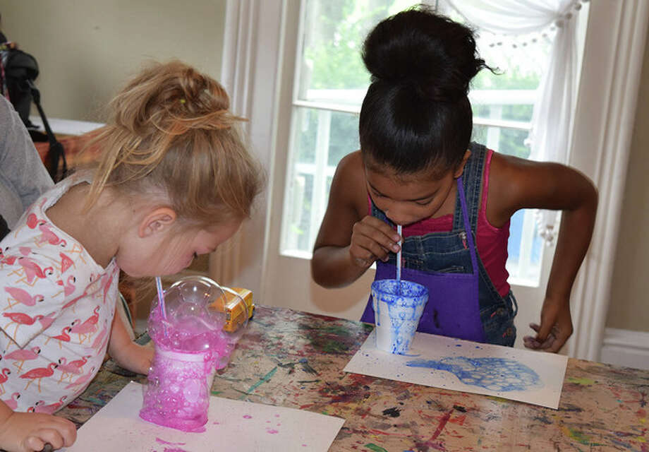 Bailey Miller (left), 4, and Jaycee Jackson, 8, blow bubbles in paint to create art Saturday at the Asa Talcott House. Photo: Samantha McDaniel-Ogletree | Journal-Courier