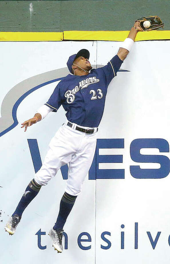 The Brewers' Keon Broxton reaches over the wall to catch a ball hit by the Cardinals' Jose Martinez in the second inning of Thursday's 2-1 Brewers victory in Milwaukee. Photo: Jeffrey Phelps | AP Photo