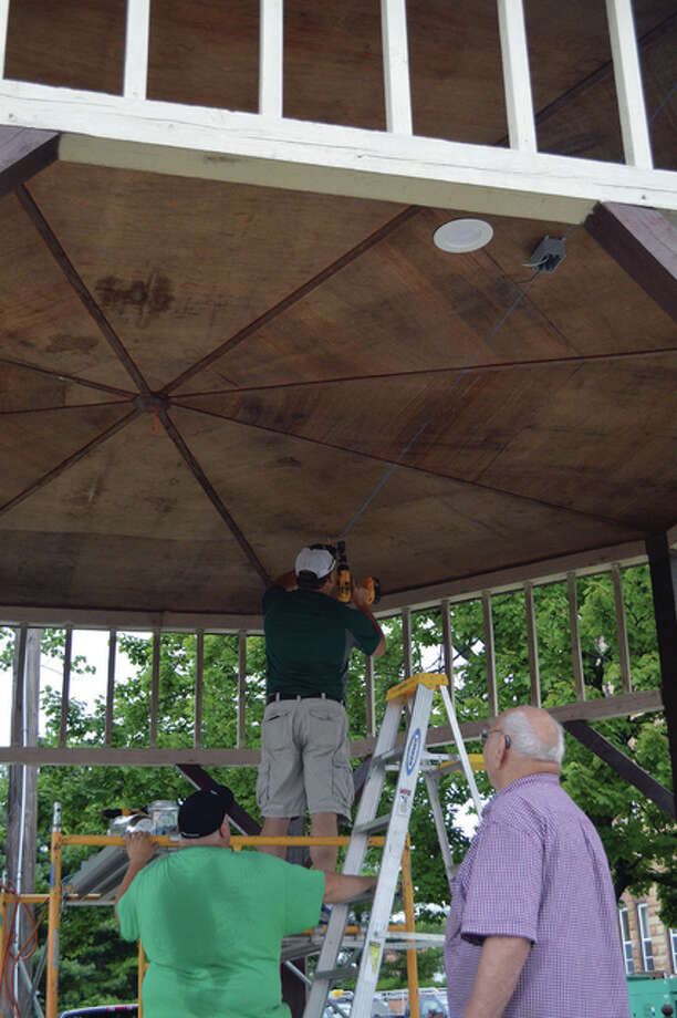 A trio of workers takes advantage of a break in the weather to upgrade the Carrollton Lions Club Gazebo on the corner of the courthouse square. Scott Rhoads is atop the ladder with Jason Young and Albert Roth assisting in adding lighting to the 11-year-old structure. The gazebo is the site of the club's summer concert series. The next concert will be Sept. 10 in conjunction with Greene County Days.