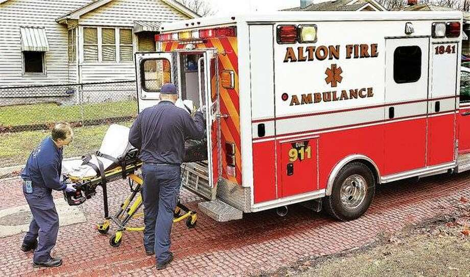 Alton firefighters load a patient onto one of the two city-owned ambulances on Jan. 17, 2017, the first day the Alton Fire Department began offering ambulance services. File photo by John Badman/The Telegraph