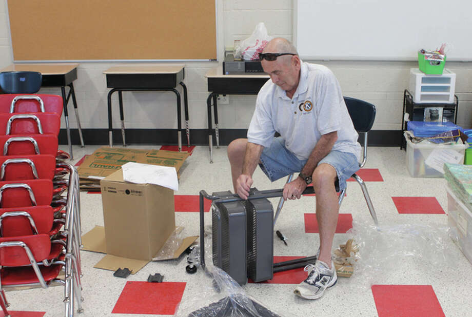 In Jessie Brown's first grade classroom at Lincoln Elementary School, Kiwanis member Dick Cody screws together a shelving unit that will be used to store classroom supplies. About a dozen Kiwanians helped set up the school Wednesday. Classes have started for the year at some west-central Illinois schools, and will begin Monday for Jacksonville District 117 schools. Police are reminding people to watch for children walking and riding their bicycles to school and to reduce speed in school zones. The speed limit in a school zone is 20 mph from 7 a.m. through 4 p.m. on school days when children are present. They also caution to watch for slowing and stopped school buses. When approaching a stopped school bus with lights activated and sign extended, motorists must stop before reaching the school bus. Failure to do so can result in a $150 fine and the suspension of a driver's license for three months. Photo: Andrew Drea | Journal Courier