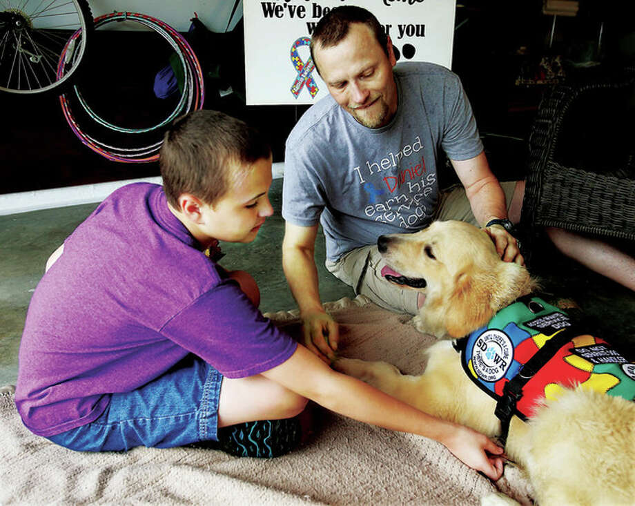 Daniel Salvato, 12, and his father, Andrew Salvato, welcome Daniel's new support dog, Wags, after the dog arrived at their home in Godfrey. Wags, a 1-year-old male golden retriever, is a specially trained autism service dog and will undergo several days of training with his new family. John Badman | The (Alton) Telegraph