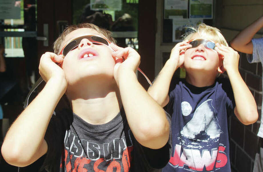 Children look at the sun using special eclipse glasses during a program at the Watershed Nature Center in Edwardsville. The center held programs for educators and children Tuesday, in anticipation of the Aug. 21 solar eclipse.