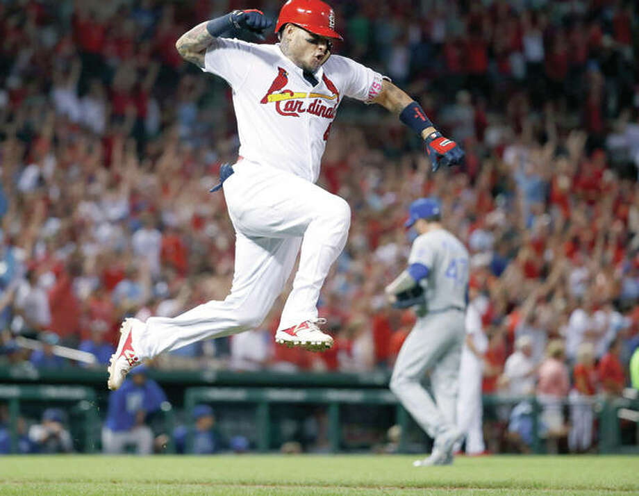The Cardinals' Yadier Molina, left, celebrates after hitting a grand slam off Kansas City Royals relief pitcher Peter Moylan in the sixth inning of Wednesday night's win in St. Louis. Photo: AP