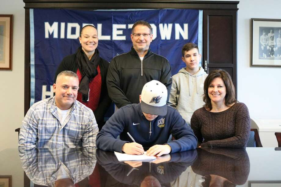 Middletown High School senior Mike Aresco, a record-breaking kicker for the Dragons, announced he has committed to play football at Merrimack College. He is seen signing a National Letter of Intent surrounded by his father Scott Aresco and mother Cheryl Aresco. Athletic Director Elisha De Jesus, football coach Sal Morello and Mike's brother, Matt Arescoare standing. Photo: Submitted