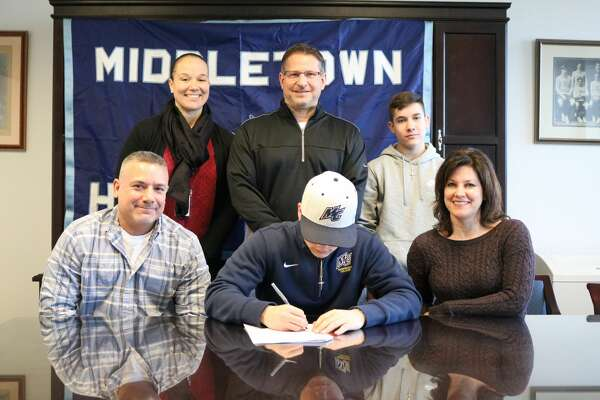 Middletown High School senior Mike Aresco, a record-breaking kicker for the Dragons, announced he has committed to play football at Merrimack College. He is seen signing a National Letter of Intent surrounded by his father Scott Aresco and mother Cheryl Aresco.   Athletic Director Elisha De Jesus, football coach Sal Morello and Mike's brother, Matt Arescoare standing.