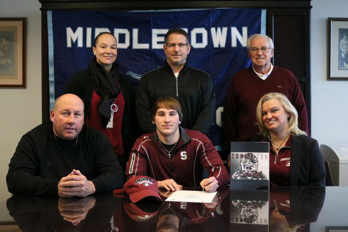 Stone Belzo, a senior at Middletown High School, has commited to play football at Springfield College. He is seated with his father, Mike Belzo and mother, Robin Belzo. Athletic Director Elisha De Jesus, football coach Sal Morello, and Stone's grandfather, Mike Belzo are standing.