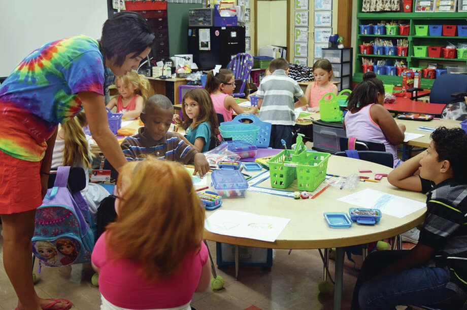 First-grade teacher Lauren Beavers helps students with a project Tuesday at Washington Elementary School. Photo: Samantha McDaniel-Ogletree | Journal-Courier