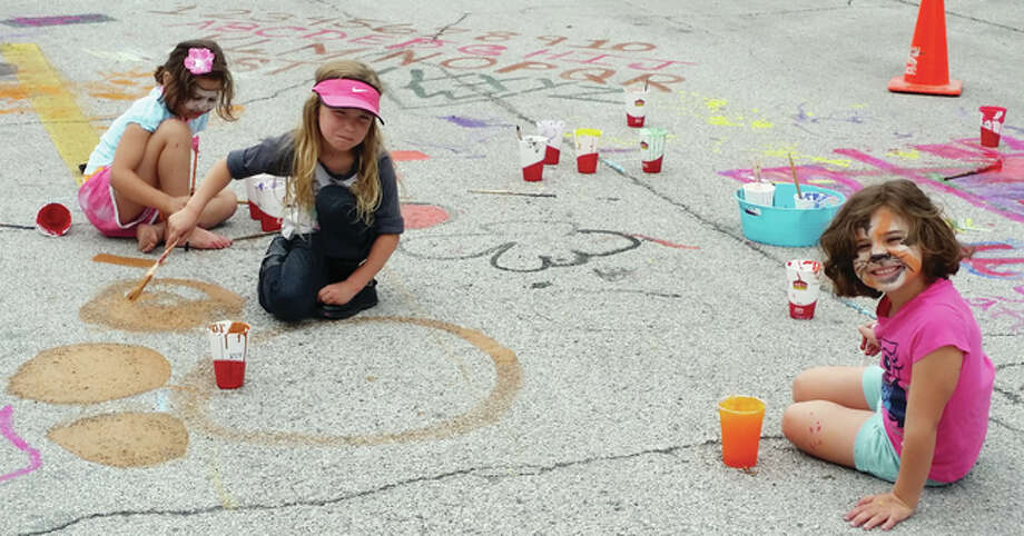 Paint decorates the street — and some of the painters — during Beardstown's 2015 Art in the Park event on the downtown Beardstown square. Event organizers are teaming up with Taste of Beardstown on Saturday to fill the square with activities. Photo: Submitted Photo