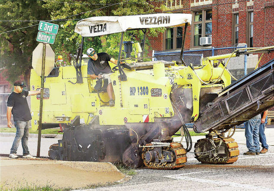 An employee of CSR Asphalt Paving in Godfrey holds the stop and street sign out of the way of an asphalt stripper this week as he clears the top layer of asphalt off East Third Street near Henry Street in Alton. CSR and dump trucks from the Alton Public Works Department were busy stripping the top layer of asphalt off East Third Street between Henry and Langdon streets in preparation for re-paving. Other parts of the street will get re-paved but workers were focusing on finishing the section next to St. Mary's Catholic School before the start of the school year which brings a lot of traffic to that block.