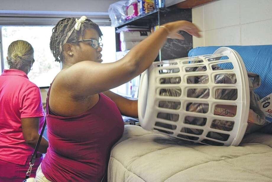Redell Hendricks of Edwardsville unloads a basket of back-to-school essentials on a residence hall bed at Illinois College. She was helping her brother, Harold Hendricks, move into his room Thursday. Photo: Samantha McDaniel-Ogletree | Journal-Courier
