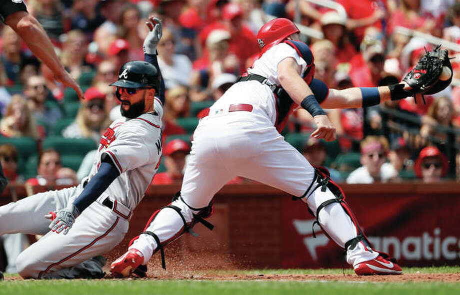 The Braves' Nick Markakis (left) scores past Cardinals catcher Carson Kelly during the fourth inning Sunday afternoon at Busch Stadium. Atlanta won to halt St. Louis' winning streak at eight in a row. Photo: Associated Press