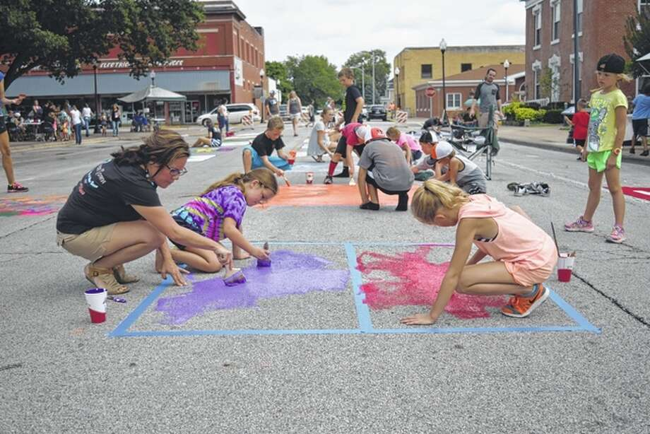 Bree McClenning (from left), Addi McClenning, 8, and Mylee Tracy, 8, paint a square on the street Saturday as part of the Art in the Park event in downtown Beardstown. Addi is the daughter of Bree and Joe McClenning of Beardstown and Mylee is the daughter of Brooke and Bryan Tracy of Beardstown. Photo: Greg Olson | Journal-Courier