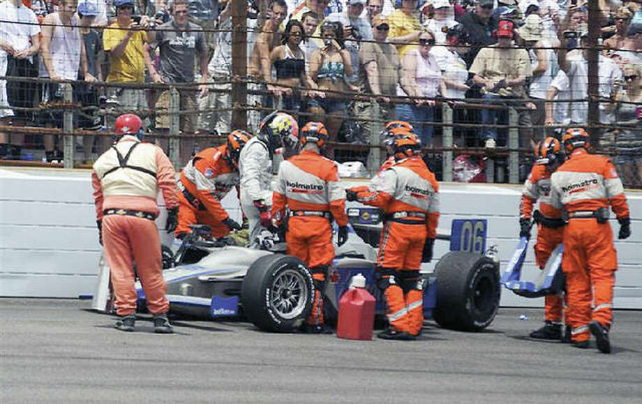 Members of the Holmatro Safety Team help IndyCar James Hinchcliffe of Sprott Newman/Haas racing climb from his car after he hit a wall during practice for the 2015 Indianapolis 500. The Holmatro team will be on hand at the Bommarito 500 Aug. 26 at Gateway Motorsports Park. Photo: AP File Photo