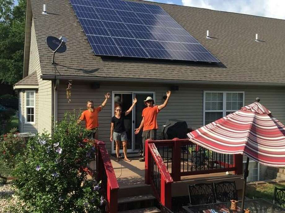 Julie Zimmerman, center, celebrates the look and value of her home's new 5.7 KW Solarize Madison County/Glen Carbon solar array. Photo: StraightUp Solar | For The Telegraph