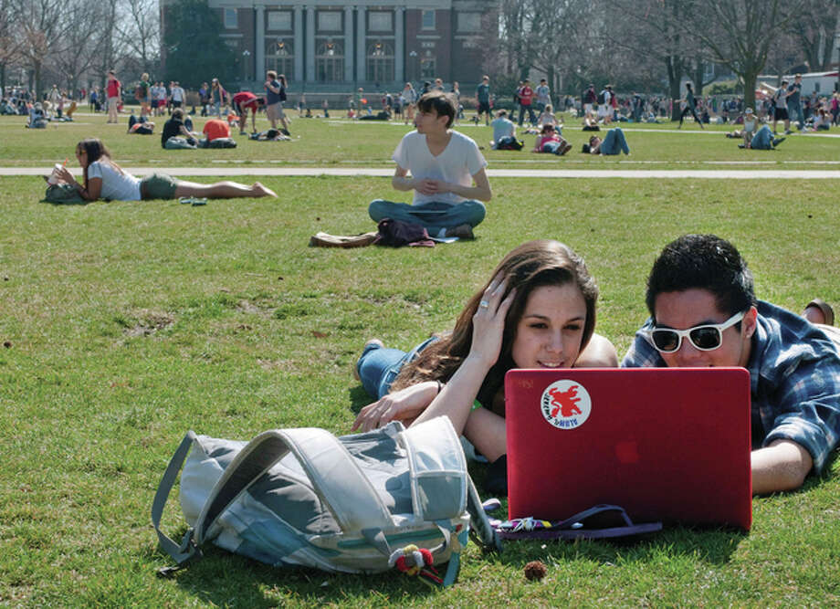 Robert K. O'Daniell | The News-Gazette (AP) University of Illinois students study on the Quad on campus in Urbana. The Illinois law that locks in tuition rates for in-state students appears to have the unintended effect of driving up tuition and fees for some students, according to a pair of studies from University of Illinois researchers. The law guarantees that a student starting as a freshman at a state university in Illinois will pay the same tuition rate for four years.