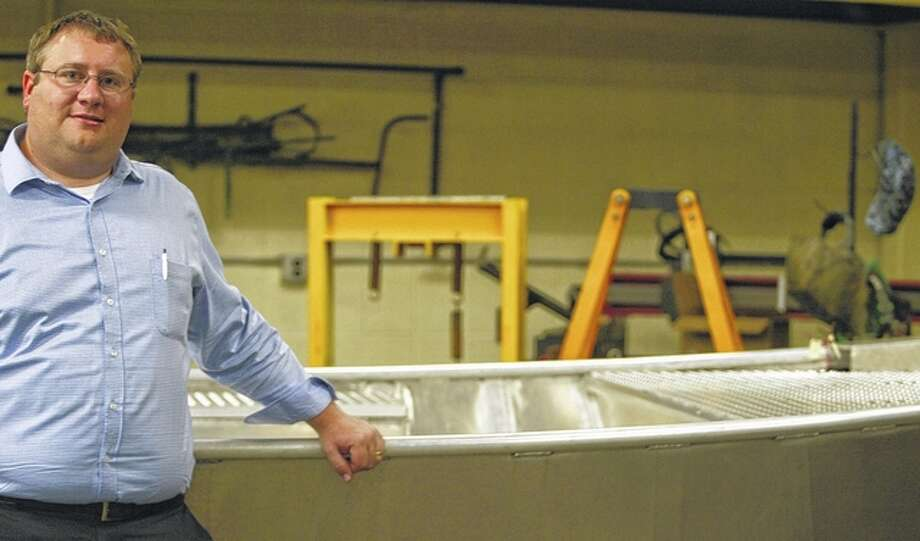 Journal-Courier Former Jacksonville High School industrial arts teacher Jacob Sitze stands next to a boat that was built by students as part of a year-long project.