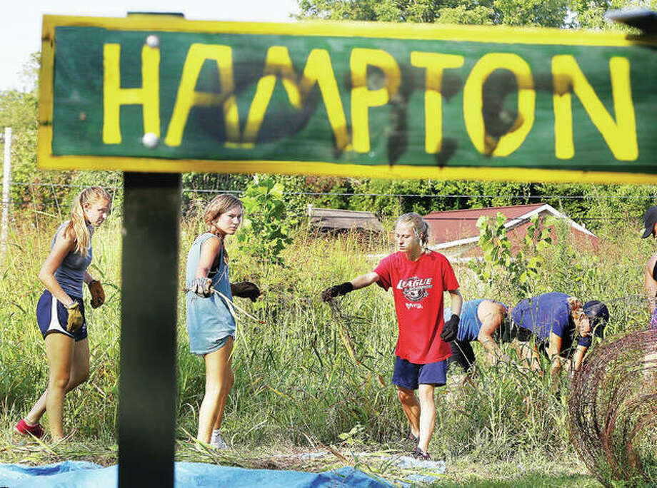 Soccer players from Principia College in Elsah pull weeds in the highly overgrown Hampton Garden on Hampton Street in Alton Tuesday. The community garden has become overgrown with grass and weeds taller than most of the students. Pride Inc., workers from the city of Alton and an Alton alderwoman also participated in the cleanup. Some students worked to re-paint the sign, which had been vandalized by graffiti. Photo: John Badman | The Telegraph