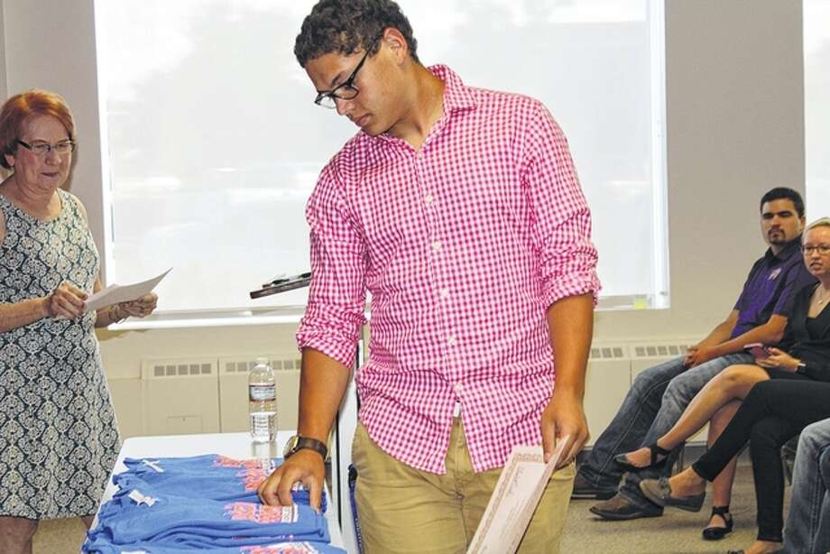 Noah Pickens, a freshman at Illinois College, pick out a Jacksonville Promise shirt after receiving a Jacksonville Promise scholarship Thursday at Lincoln Land Community College. Photo: Samantha McDaniel-Ogletree | Journal-Courier