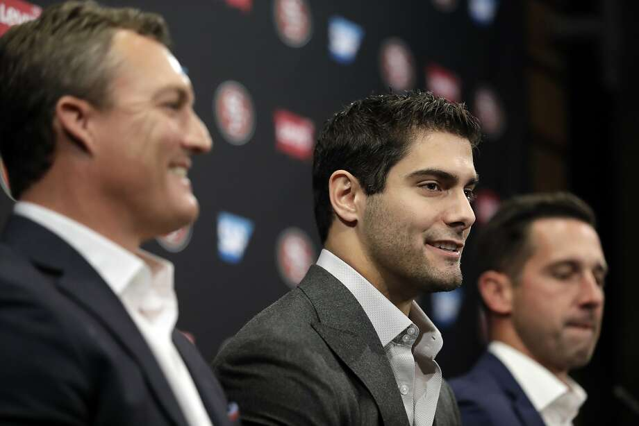 49ers quarterback Jimmy Garoppolo (center) is surrounded by general manager John Lynch and head coach Kyle Shanahan after signing a five-year contract worth $137.5 million. Photo: Marcio Jose Sanchez, Associated Press