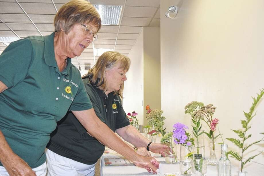 Morgan County Garden Club members Anita Moody of Chapin and Joyce Giner of Jacksonville prepare flowers for the club's annual show Friday. This is the first year the show was been featured at Lincoln Land Community College. Divisions included annuals, herbs, roses, perennials and arrangements. Photo: Nick Draper | Journal-Courier