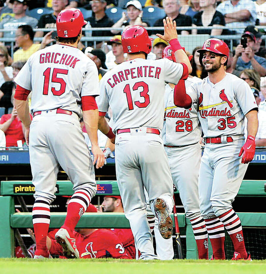 The Cardinals' Matt Carpenter (13) is greeted by teammates Randal Grichuk (15) and Greg Garcia at home after hitting a three-run homer against the Pirates in the second inning Friday. Photo: AP