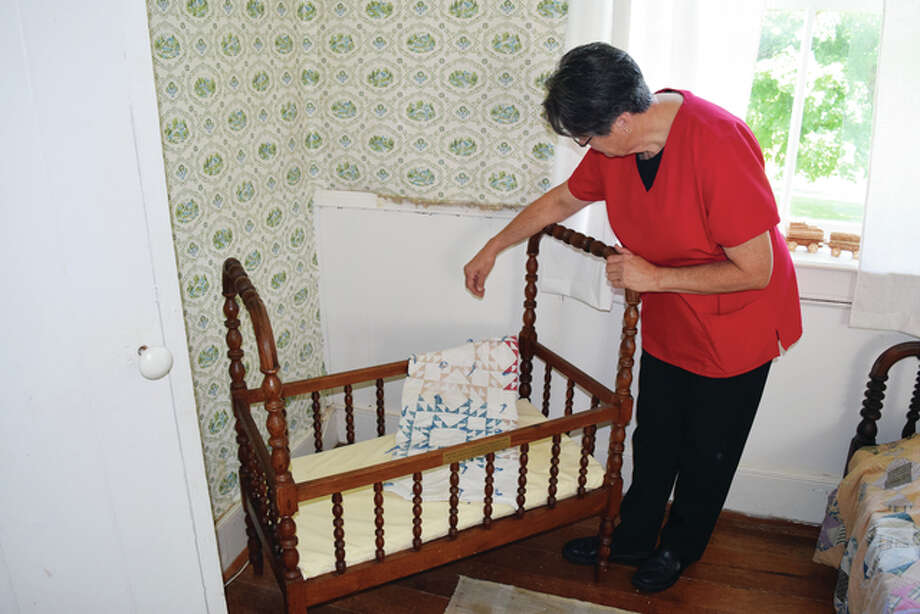 Theresa Schroeder, a member of the Underground Railroad Committee's house subcommittee, looks at the recently donated 1870s cradle that belonged to the Huffaker family who founded Woodlawn Farm. The Woodlawn Farm/Underground Railroad Committee Fall Festival is Saturday. Photo: Greg Olson | Journal-Courier
