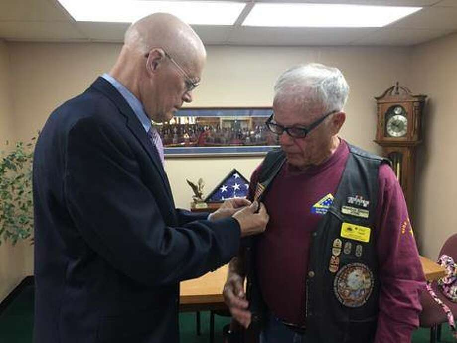 State Sen. Bill Haine, D-Alton, left, places an honorary pin on the vest of Patriot Guard Rider and Alton native Fred Smith. Photo: For The Telegraph