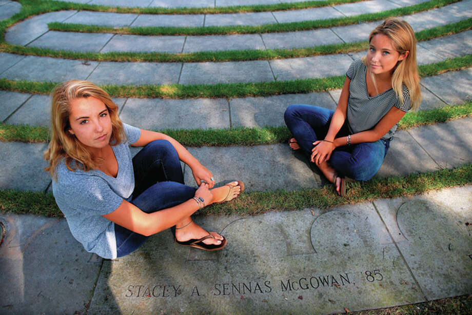 Jonathan Wiggs | The Boston Globe (AP) Sisters Ryan (left) and Casey McGowan sit beside the stone honoring their mother on the Boston College campus in Boston on Sept. 4, 2015. Their mother, Stacey Sennas McGowan, was killed on during the attacks on the World Trade Center on Sept. 11, 2001.