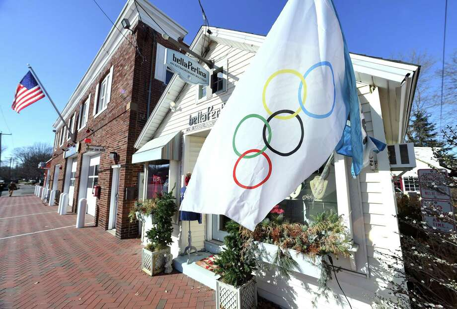 An Olympic flag is displayed in front of the boutique, bella Perlina, in downtown Madison on February 8, 2018 in support of the three Madison athletes competing in the Winter Olympics. Photo: Arnold Gold / Hearst Connecticut Media / New Haven Register