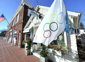 An Olympic flag is displayed in front of the boutique, bella Perlina, in downtown Madison on February 8, 2018 in support of the three Madison athletes competing in the Winter Olympics.
