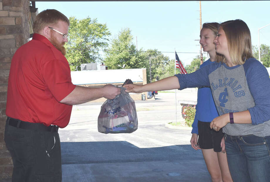 Aaron Stoecker, an emergency medical technician for American Ambulance Service, accepts a bag of snacks and thank yous from Illinois College student Melissa Urban (right) and Grace Graunke on Monday. The students handed out bags to emergency responders around Jacksonville and South Jacksonville in recognition of the anniversary of the Sept. 11, 2001, terror attacks.