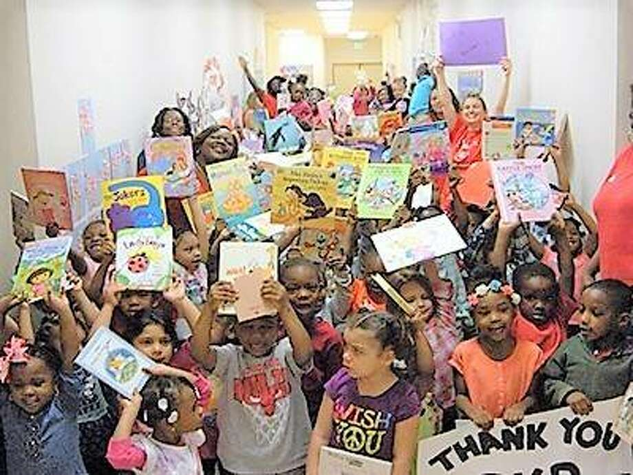 Children in the SIUE Head Start/Early Head Start Program happily display books that have been donated to them. Photo: For The Telegraph