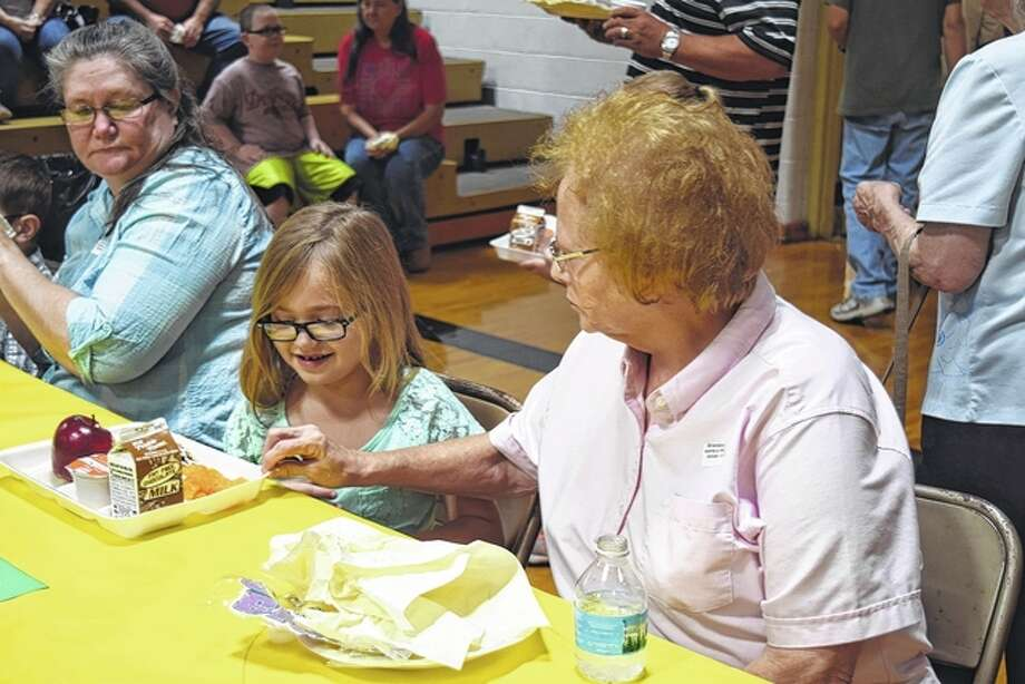 Delores Hoots encourages her granddaughter, Autumn Hoots, to finish her breakfast Thursday at the Winchester Elementary School's Grandparents Day. Photo: Samantha McDaniel-Ogletree | Journal-Courier