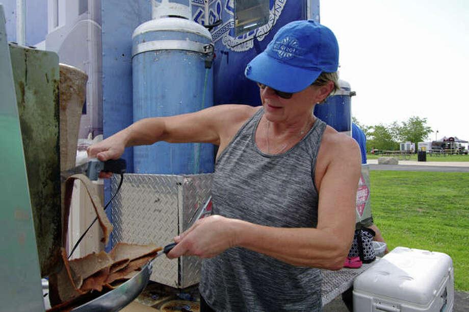 Anna Zavradinos carves meat for the Go Gyro Go food truck