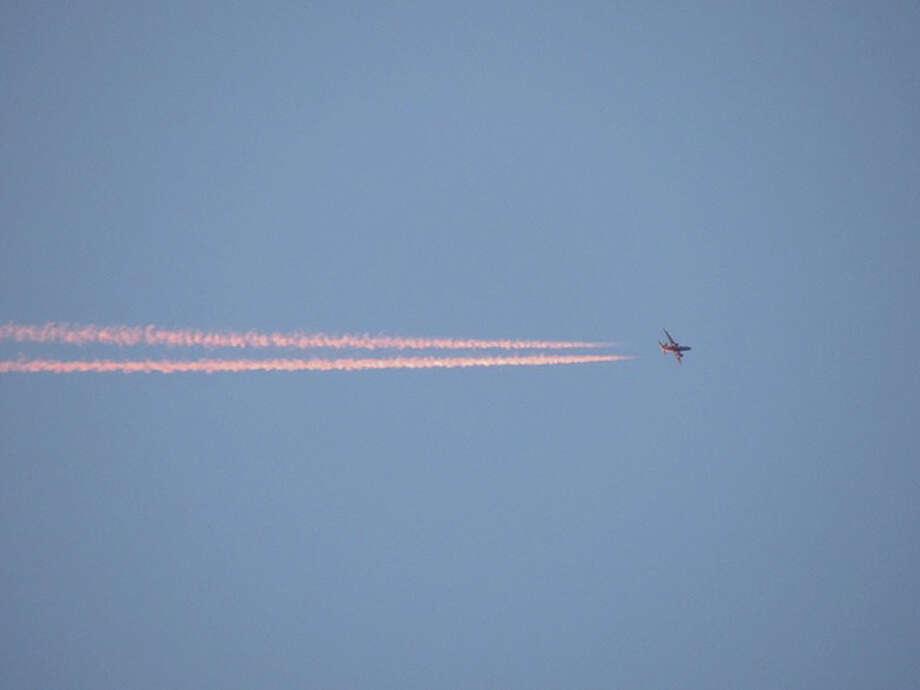 A plane's vapor trails capture the colors of the setting sun.