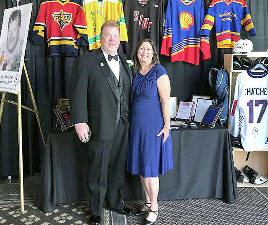 Larry Thatcher and his wife Paula stand in front of a display of some of his career memorabilia at the St. Louis Amateur Hockey Hall of Fame induction ceremony Saturday in St. Louis. Photo: Submitted Photo