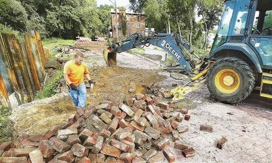 A construction worker piles up bricks as a backhoe works next to him on the badly eroded section of Summit Street in Alton Tuesday. Work is resuming on the massive project to replace the sewer and water lines under the street, stop the erosion and repair the street which has been closed for over a year. Photo: John Badman | The Telegraph