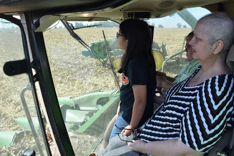 "Valerie Eyer (left), the 13-year-old daughter of Gwenn and Glenn Eyer of Jacksonville, rides in a combine Thursday with her mom (right) and Jon Freeman during the harvesting of a Coultas farm cornfield in South Jacksonville. The ride was given as part of a Harvest Day event sponsored by the Jacksonville Area Chamber of Commerce's Agri-Industry Division, the Cass-Morgan Farm Bureau and Freeman Seed Co. Woodson-area farmers Jon and Sue Freeman and their son, Jacob, and daughter-in-law, Kaila, hosted the first-ever Harvest Day, during which people could take a ride in a combine and a tractor. ""They got to see how technology has changed the farming industry, with satellites being used to guide tractors and combines through the fields,"" Sue Freeman said. ""Farming is the biggest industry in our area and we want the public to know where their food and other products come from."" Photo: Greg Olson 
