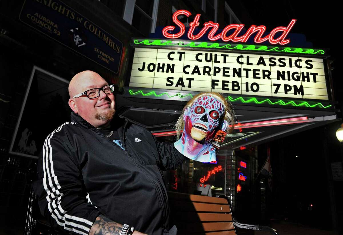 Horror film fan Larry Dwyer poses by the marquis of the Strand movie theater in SeymourTuesday.