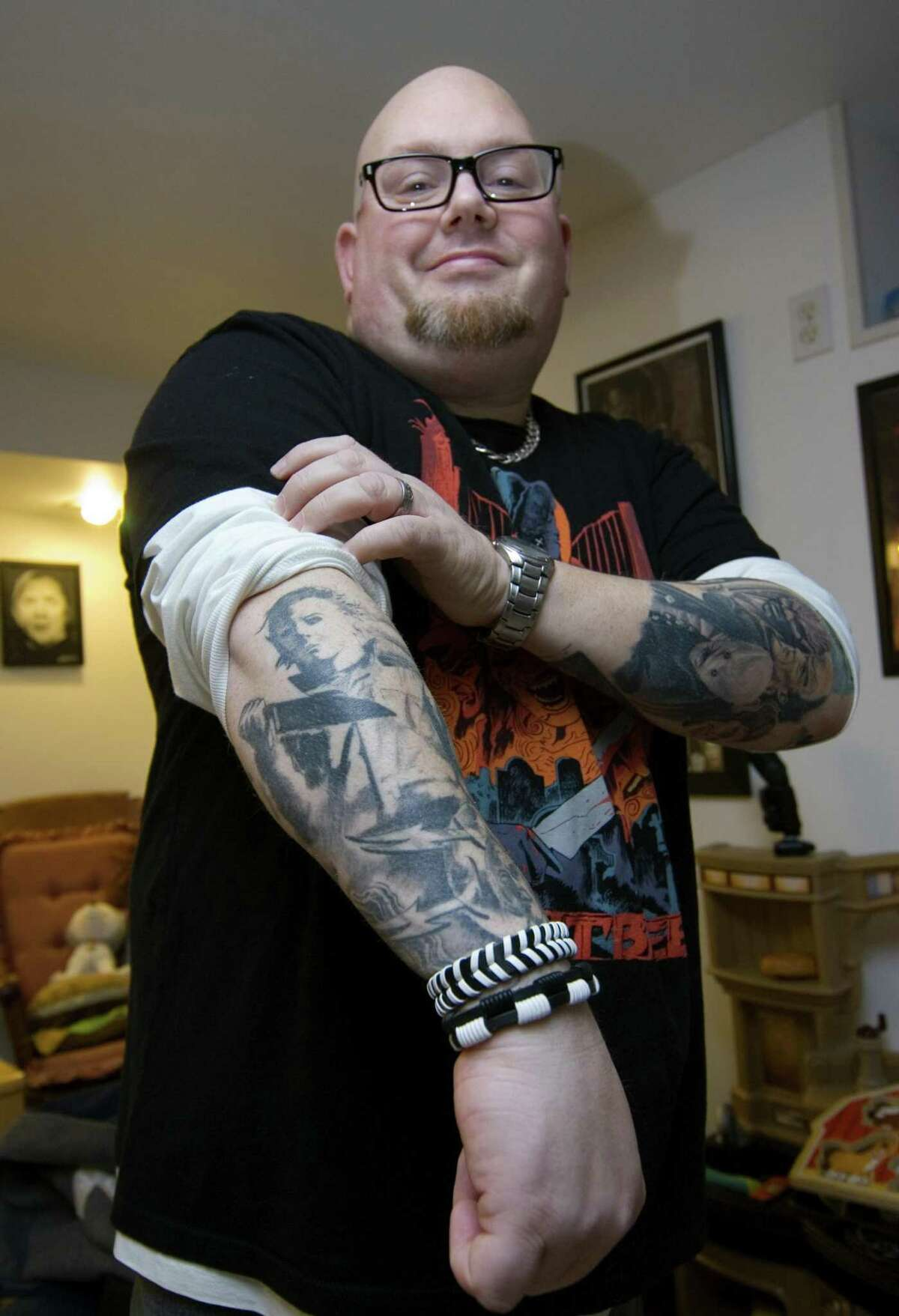 Horror film fan Larry Dwyer shows off one of his horror movie-themed tattoos at his home on Bradley Terrace in Derby on Tuesday.