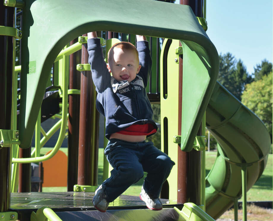 Darius Cockrill, 3, the son of Tony and Marcy Cockrill of Ashland, swings from a handlebar above a slide at Community Park on Monday. Photo: Samantha McDaniel-Ogletree | Journal-Courier